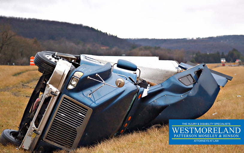 tractor trailer on its side in the median after a roll over accident