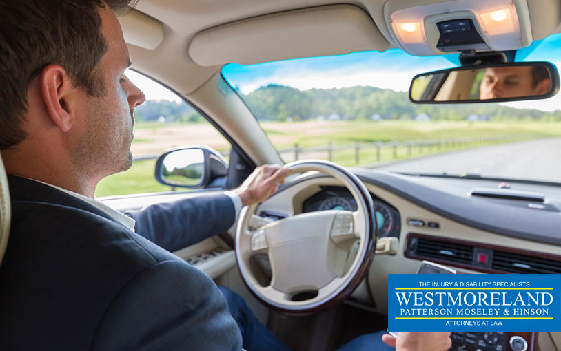 Businessman using cell phone and texting while driving not paying attention to the road